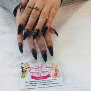 pointed long nail extensions with shimmering dark colour polish