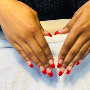 red tips design on clear nail extensions