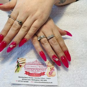 shiny bright dark pink nail polish on oval nail extensions