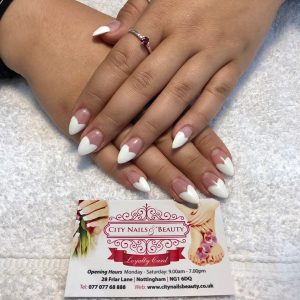 white heart tips design on pointed nail extensions